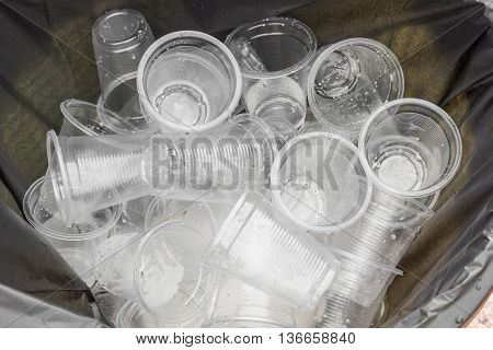 Plastic glass used for drinking water in a bin - Environmental problem concept / Non-compostable waste