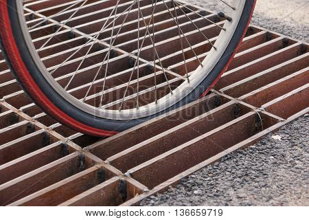 Bicycle wheel falls down and stuck in the drain lid - Bicycle accident and safety concept