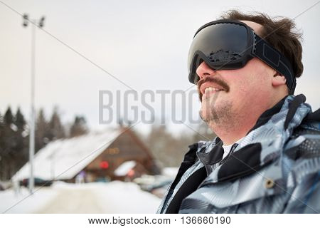 Close-up portrait of man in black ski goggles standing outdoors at ski resort.