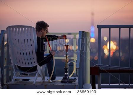 Young man adjusts burning of charcoal at hookah sitting in armchair on highrise roof at sunset dusk.