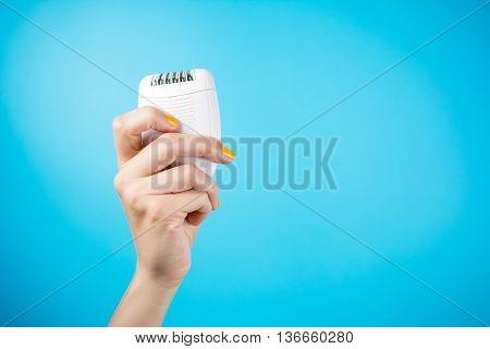 Woman Holding Epilator Against Blue Background