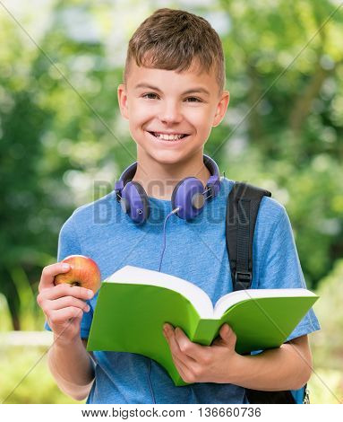 Outdoor portrait of happy teen boy 12-14 year old with book and apple. Back to school concept.