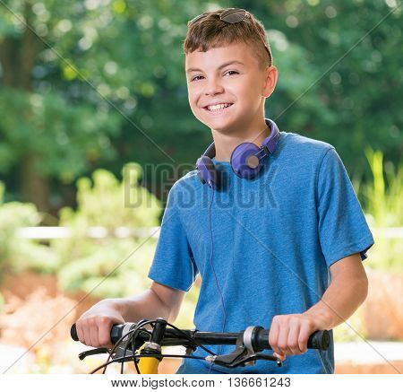 Young cyclist on a bike in the park. Teen boy 12-14 year old with bike posing outdoors.