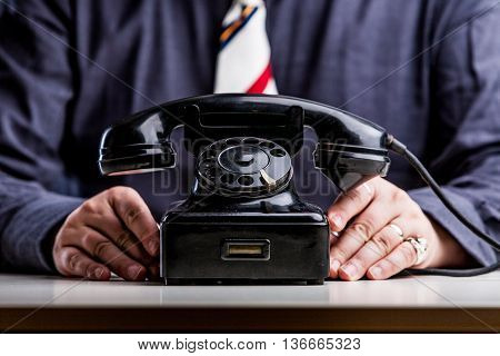 Telephone On Foreground With Hands Of An Office Worker
