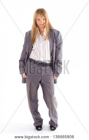 Young business woman dressed in big male suit is standing on a white background.