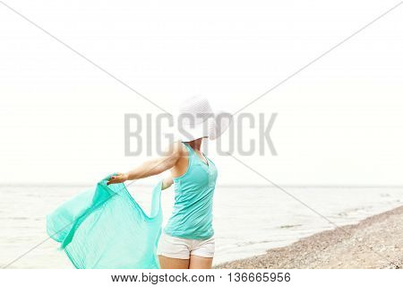 Freedom Concept. Portrait of a beautiful woman with a turquoise scarf and a big white hat on the beach enjoying the summer. Jumping on the beach. Travel and Leisure.