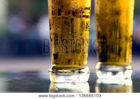 Two cold lager light beers on table on blue background.