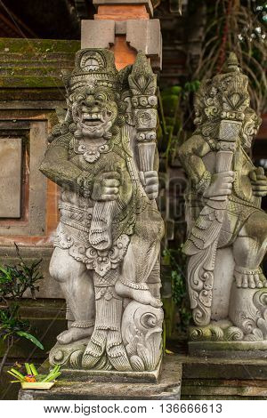 Traditional demon guards statue carved in stone in Bali.