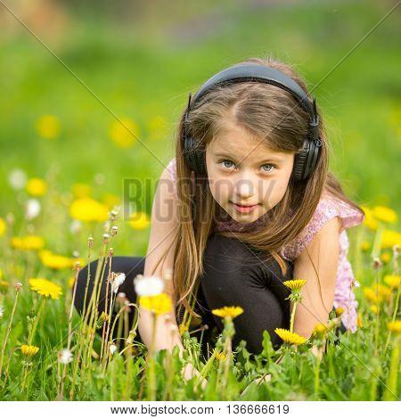 Little girl in headphones on a green meadow.