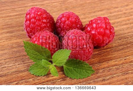 Fresh Raspberries And Lemon Balm On Wooden Surface, Healthy Food