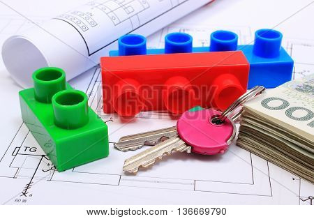 Heap of banknotes home keys plastic building blocks and electrical diagrams lying on construction drawing of house concept of building house drawings for the projects engineer jobs