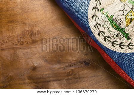 The national flag of Belize on a rough cloth. Wooden background.