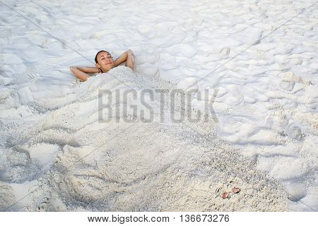 The girl lies on a white sand buried in the sand. Relax and enjoy a beach holiday.