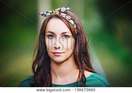 Portrait of a girl with a bow on his head gentle and young brunette the summer day