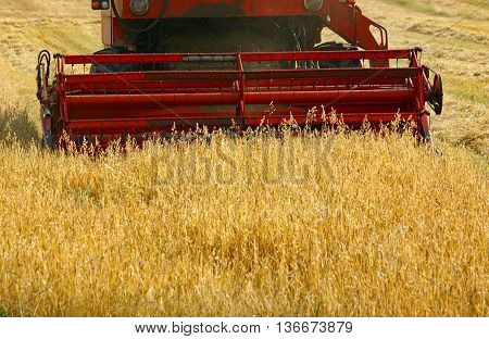 Detail of a working combine harvester in crop field