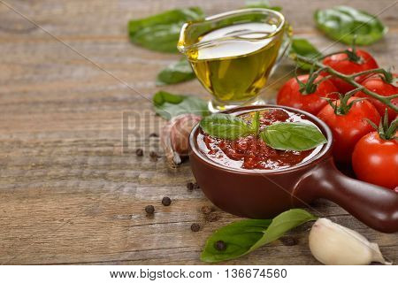 Tomato sauce with basil on a wooden background
