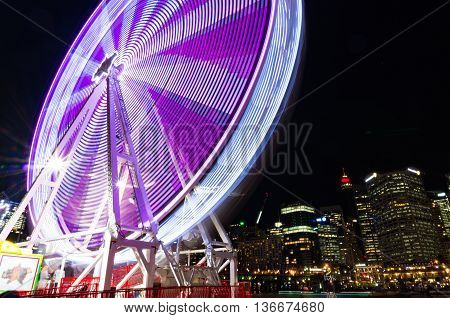 Amusement park attractions. Spinning ferris wheel at night with cityscape on the background. Motion blur