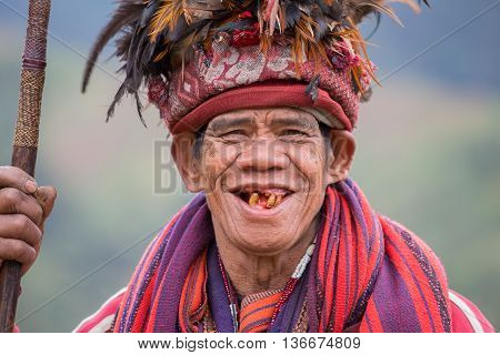 BANAUE PHILIPPINES - JANUARY 24 2014 : Unknown old ifugao man in national dress next to rice terraces. Ifugao - the people in the Philippines. Refers to the mountain peoples.