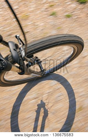 Front wheel of a bike on a dirt road with wheel shadow. View from above.