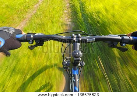 Detail of a fast motion mountain bike on a rural road between meadows