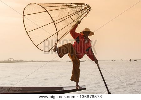 INLE LAKE MYANMAR - JANUARY 14 2016: Unidentified Burmese fisherman on bamboo boat catching fish in traditional way with handmade net. Inle lake Myanmar Burma