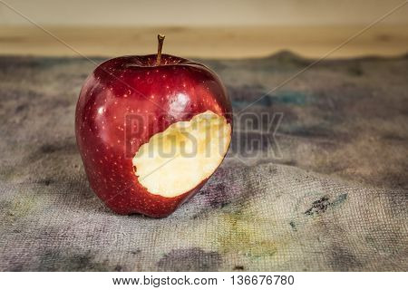 Still life photo of Traces eating red apple on cloth dirty