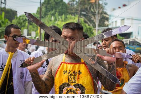 PHUKET THAILAND - OCT 18 2015: Chinese thai monk possessed by his god walks with his mouth pierced in Vegetarian Festival at Phuket Town. Festival is a famous annual also known as Nine Emperor Gods