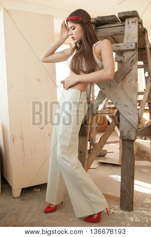 Beautiful young woman in elegant trousers posing in the ruins. Red lips. red fashion shoes.