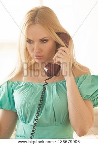 pretty blonde woman in green dress talking on old telephone. Fashion model. Sunny color.