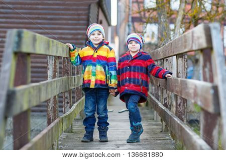 Two adorable little kid sibling boys and friends in colorful clothes standing on bridge on spring day. Twins having fun together, autumn or spring. Happy, joyful family
