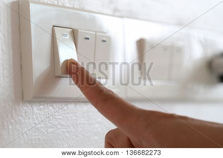 fingers are off light switch in the houseconcept for energy saving reduce global warming.