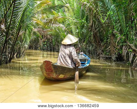 Woman paddling the Mekong Delta in Southern Vietnam