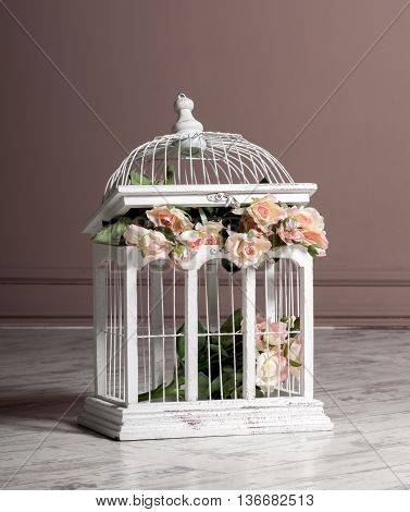 white wooden bird cage with with artificial roses inside for decoration