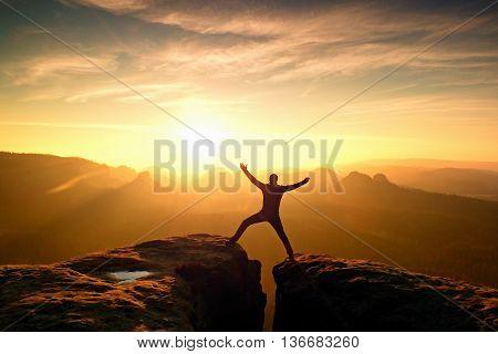 Hiker In Black Triumph Between Two Rocky Peaks