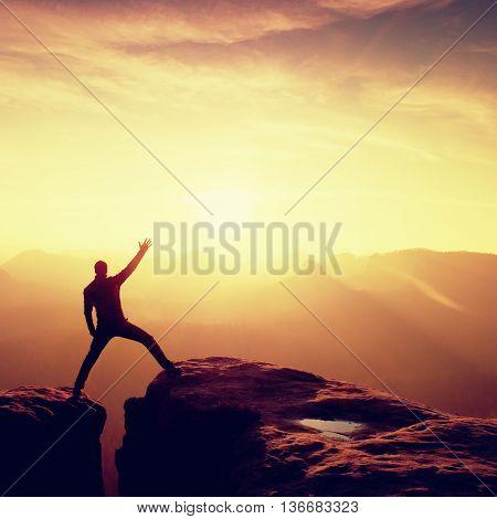 Jumping Hiker In Black Triumph Between Rocky Peaks.