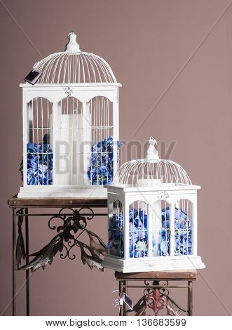 white wooden bird cages with blue hydrangeas and paraffin candle inside for decoration