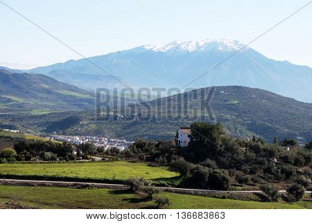 View across countryside towards the Snow capped Sierra Almijara mountains Colmenar Andalusia Spain Western Europe.