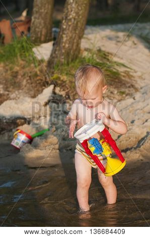 child bathes in the river with toys near the forest.