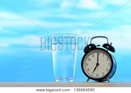 Fresh and clean drinking water in glass and alarm clock on sky background
