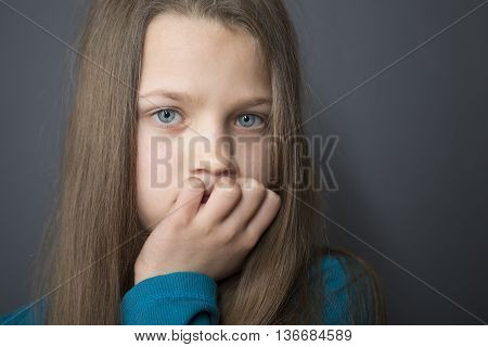 serious straight looking girl portrait with gray background