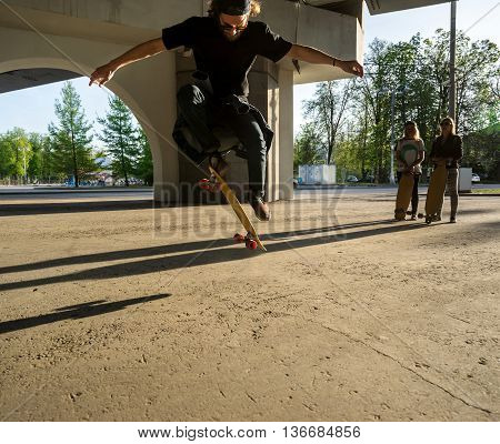 Silhouette skateboarder jumping in city on skateboard under the bridge. In the background two young girls on longboard
