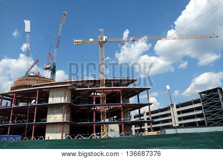Part of modern office building in business cluster over blue sky on sunny day. Horizontal view closeup