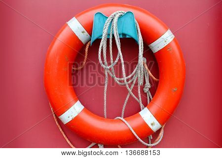 Red lifebuoy on a pink background. port