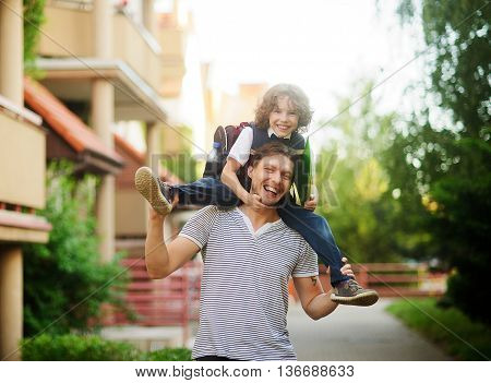 The father carries on his shoulders of his son-schooboy. Little learner with one arm hugs dad for the neck and the other holding a green folder. Father and son smiling happily. Back to school.