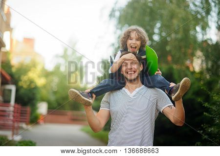 Little schoolboy sitting on the shoulders of his father. The father holds the boy's legs. The boy delighted. He likes to joke with dad. Father and son smiling happily. Back to school