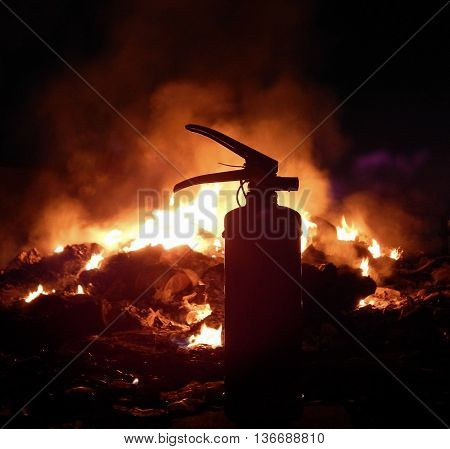 Fire extinguisher over burning flame at night