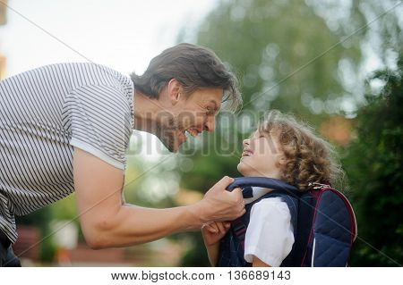 The father sees off the son-student in school. It carefully corrects for a backpack of the boy and does the ridiculous person. The small disciple looks at the daddy and laughs.