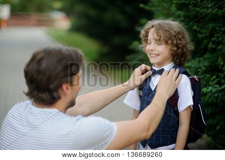 The father accompanies his son-grader to school. He sat down next to the boy and carefully straightens his bow tie. Son closed his eyes and smiles.