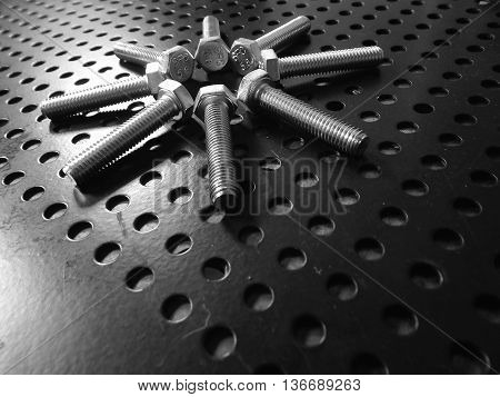 Hardware symbol. Glossy hex bolts laid out in round order on matt surface