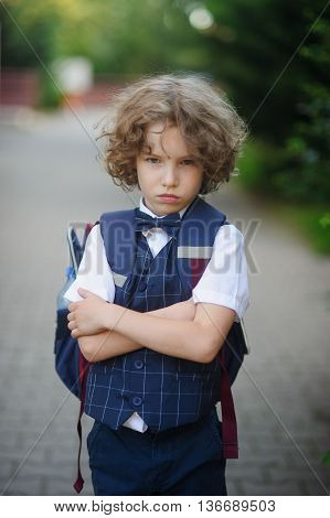Little schoolboy stands in the school yard with an angry expression on his face . The boy crossed his arms . He does not want to go to school .